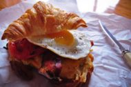 Breakfast sandwich: Fluffy croissant, fried egg, crispy bacon, hash browns
