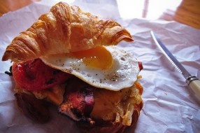 Breakfast sandwich: Fluffy croissant, fried egg, crispy bacon, hash browns