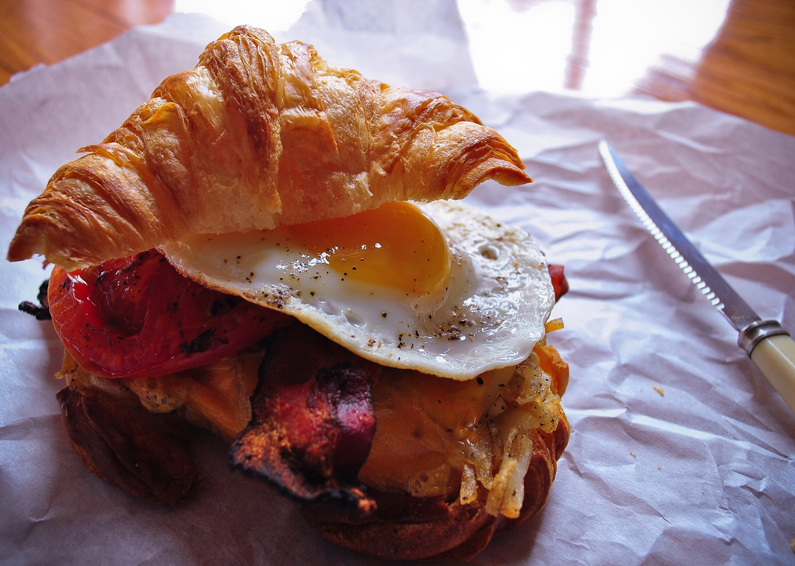 Fluffy croissant breakfast sandwich with crispy bacon, fried egg and hash browns