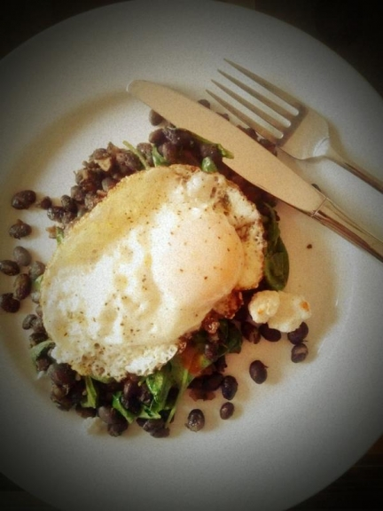Chile and cumin-spiced black beans with wilted arugula + Cholula, feta, and a fried egg